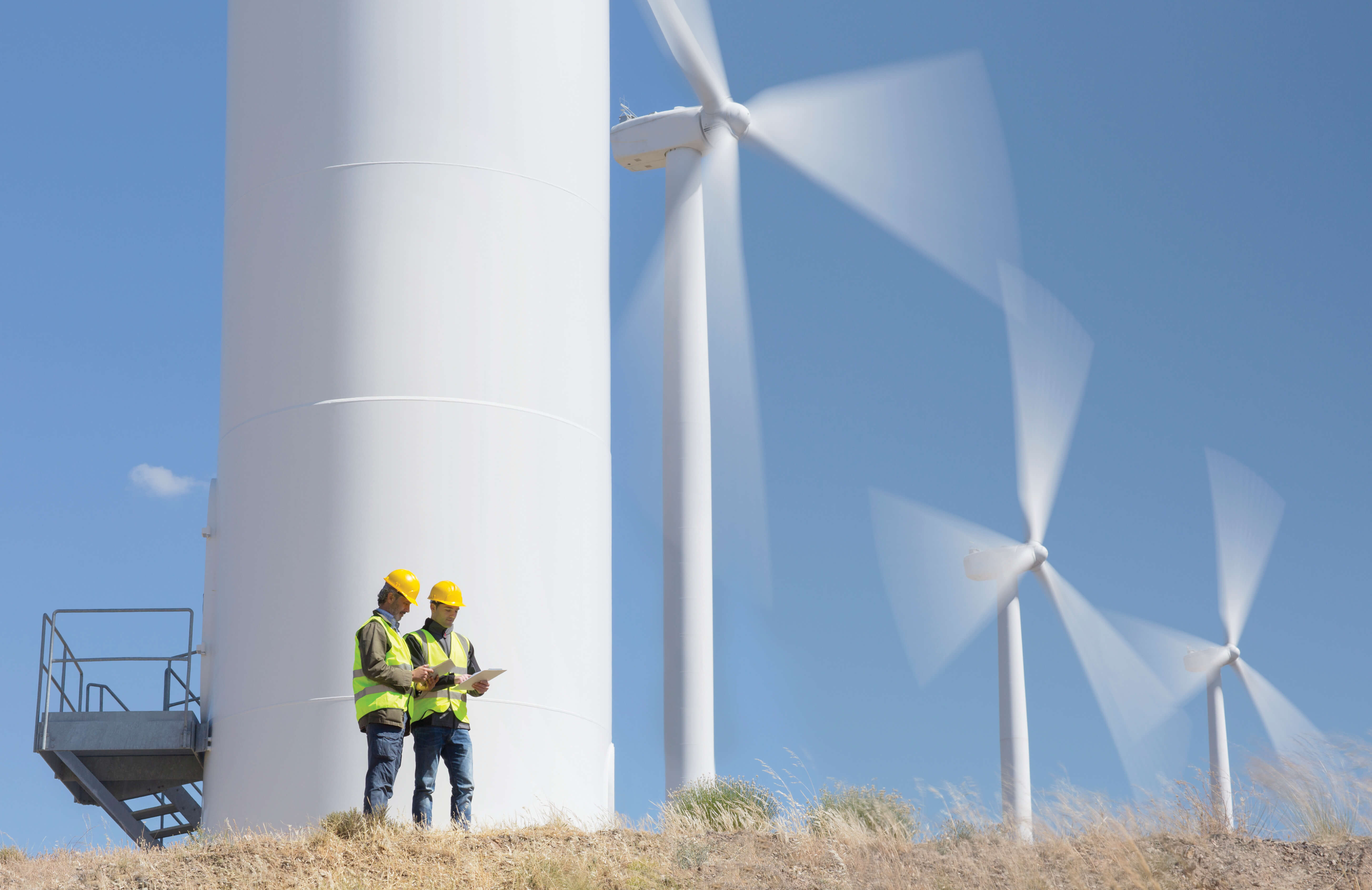 6113-07160928 © Masterfile Royalty-Free Model Release: Yes Property Release: Yes Workers talking by wind turbines in rural landscape